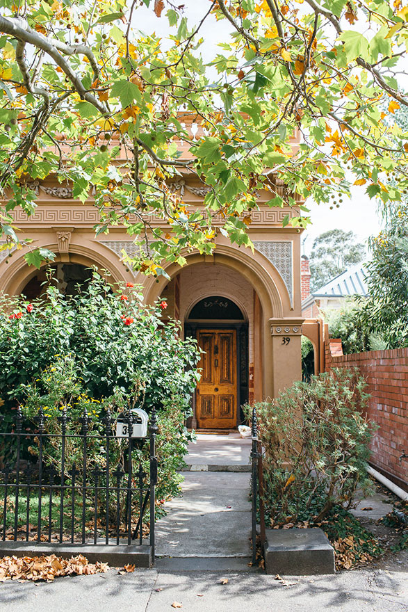 Home with large archway entrance and leafy surrounds