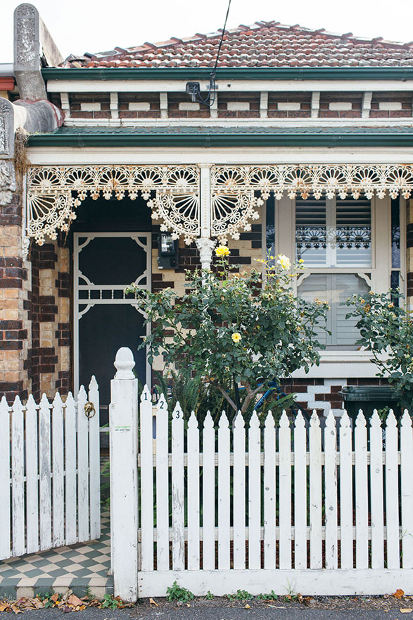 White picket fence and creamy iron lattice design feature on this housefront