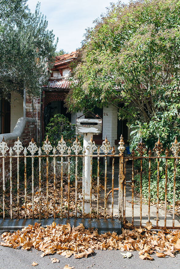 Autumn leaves fill the footpath in front of rickety iron fence and letterbox