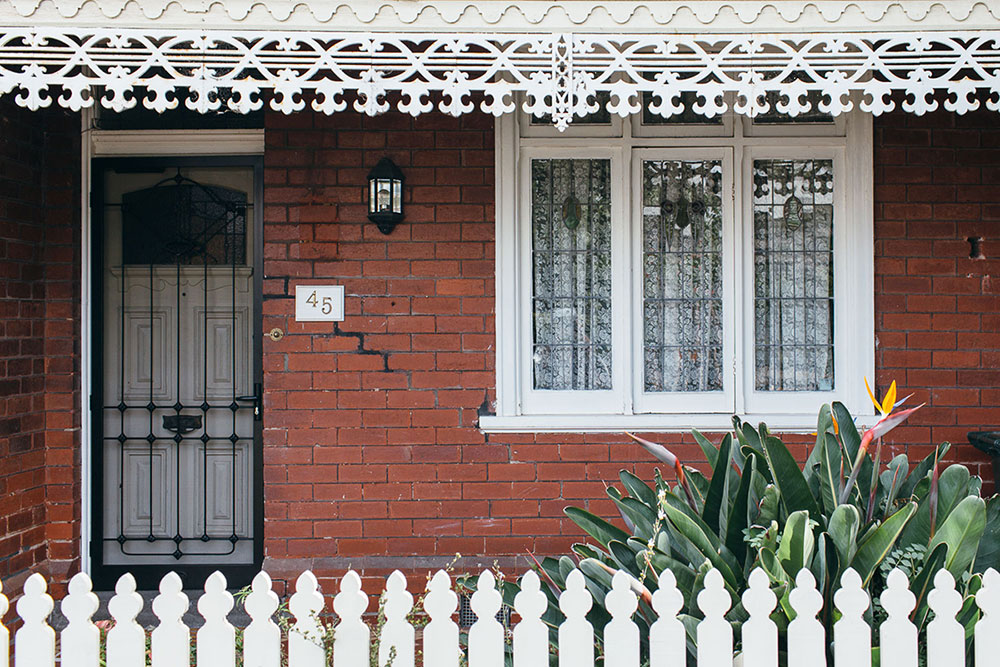 Red brick home with white fence, lattice and window detailing