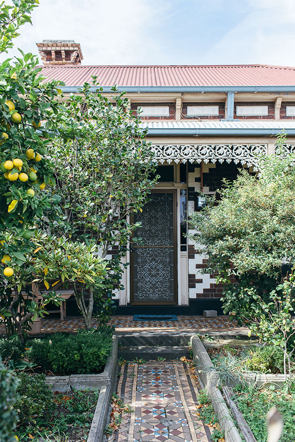 Tiled path leading up to house entrance with fruit trees