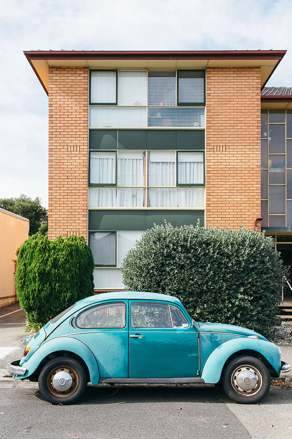 Bright aqua Volkswagen parked outside blonde brick apartment block
