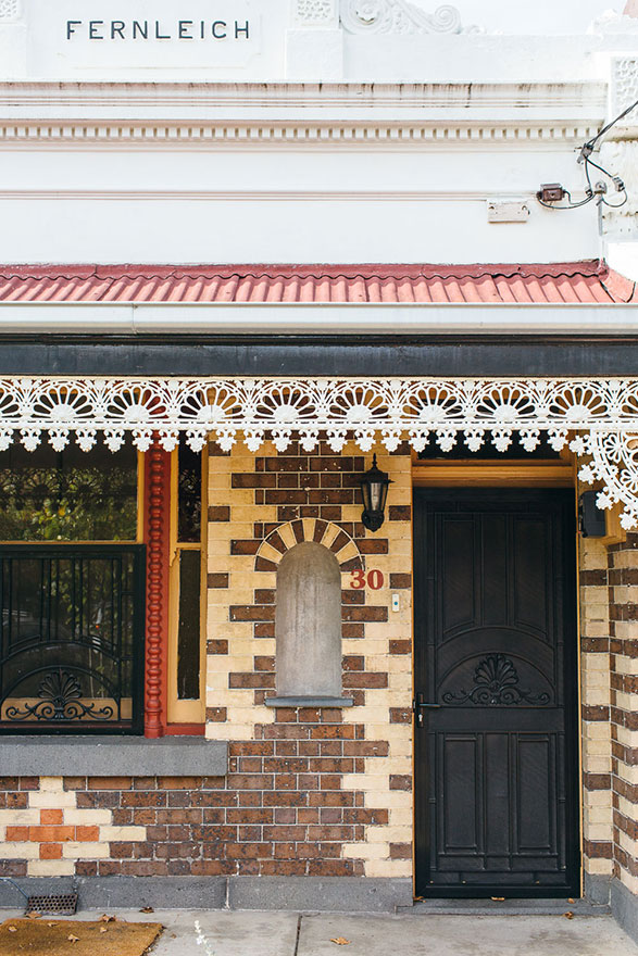 Dark and blonde brick detailing with white iron lattice housefront
