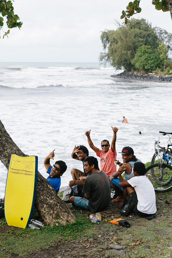 A group of friends watch local surfers off the coast of Tahiti