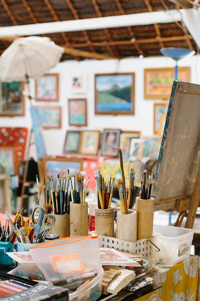 Paint brushes and pastels sit on the desk of an artists studio