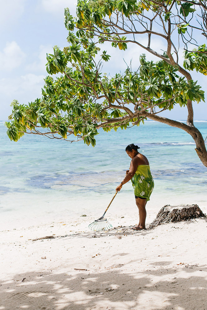 A local Tahitian woman sweeps on the beach