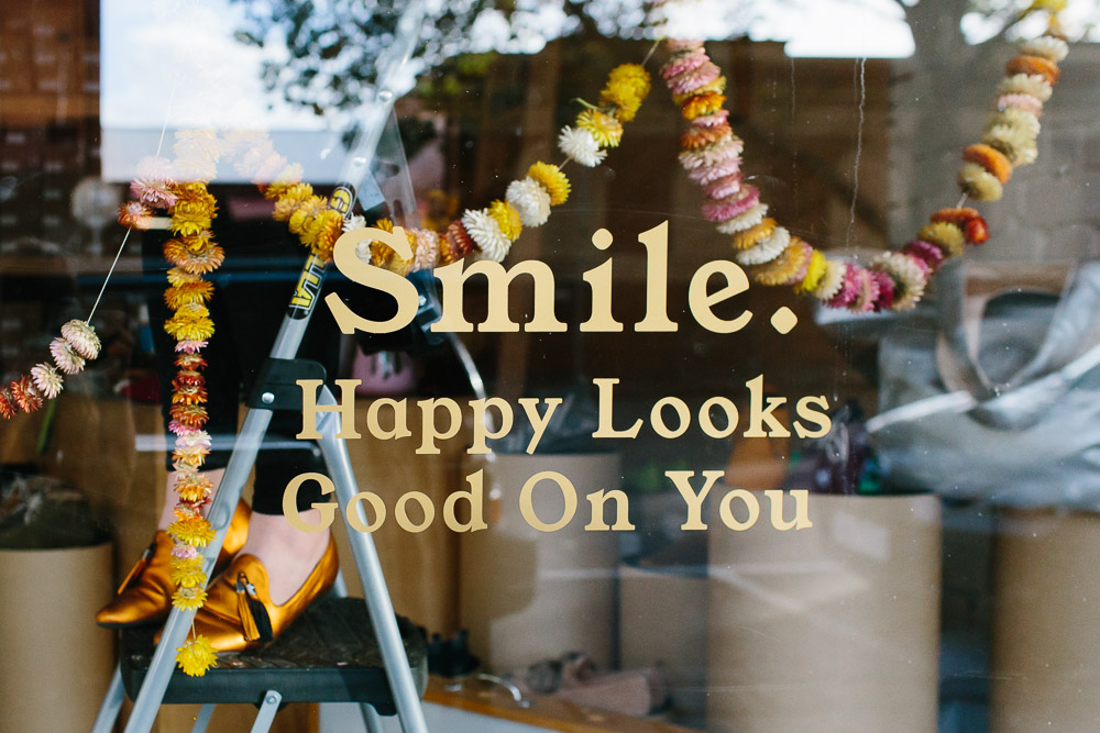 On the window at the Radical Yes store reads - Smile, Happy Looks Good On You