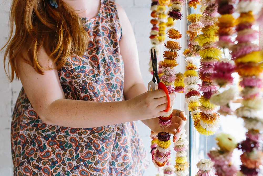 Florist hanging colourful strawflower garlands in Radical Yes storefront