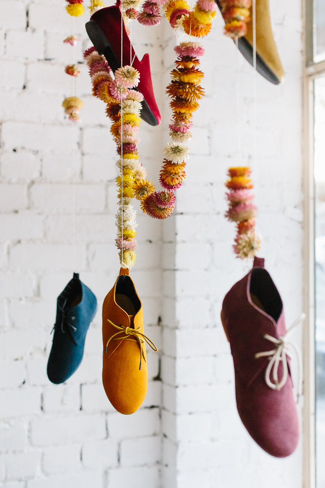 Shoes by Radical Yes hang amongst strawflower garlands in their store window