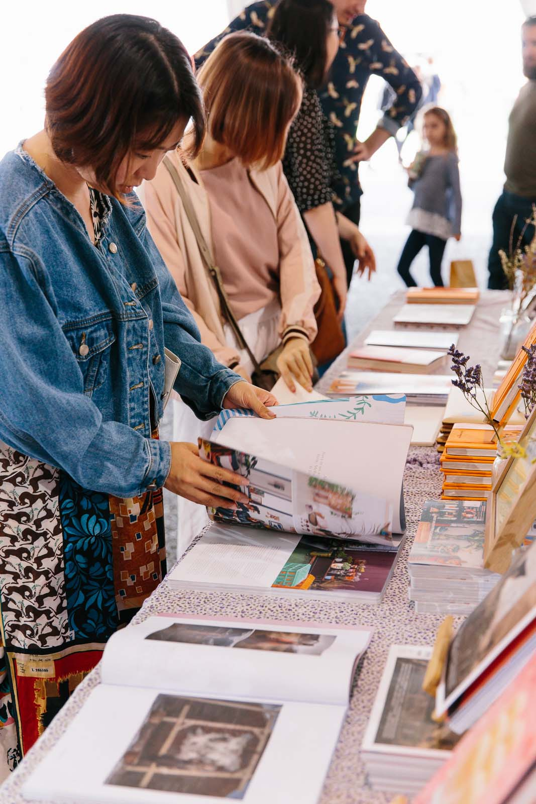 Market goers looking at books at the Frankie Magazine stall