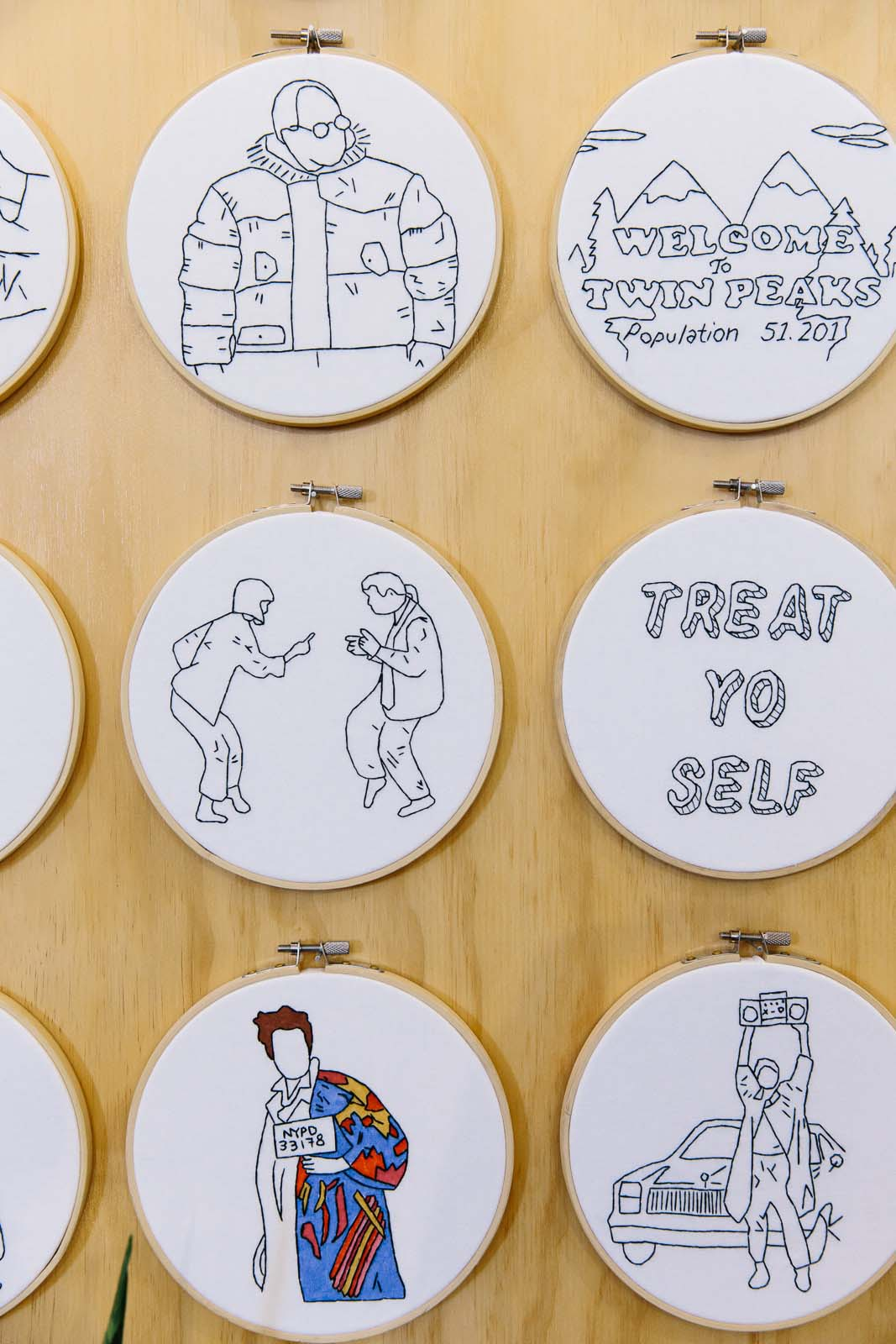 Handmade embroidered artworks with Seinfeld references and quirky illustrations