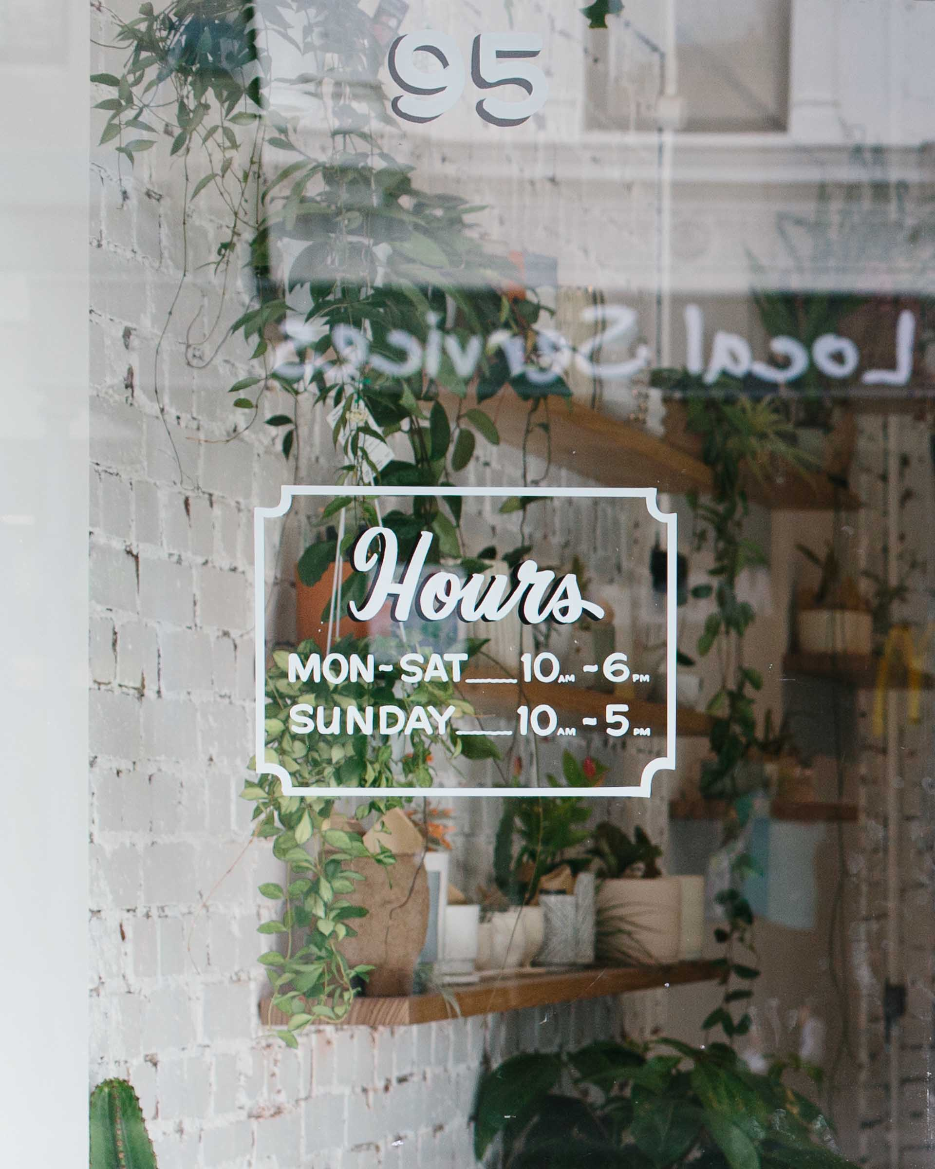 Shop front opening hours, hand painted signage