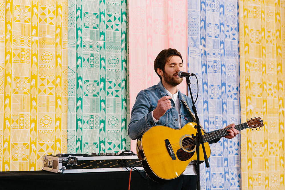 Musician plays to the crowd with colour handprinted stage backdrop