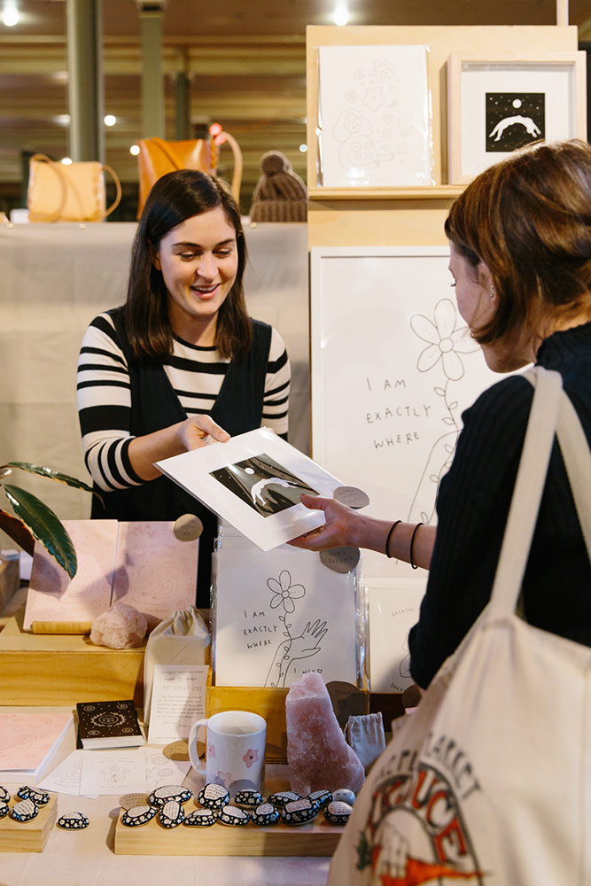 Jenna from Musings from the Moon shows a customer one of her illustrated prints for sale