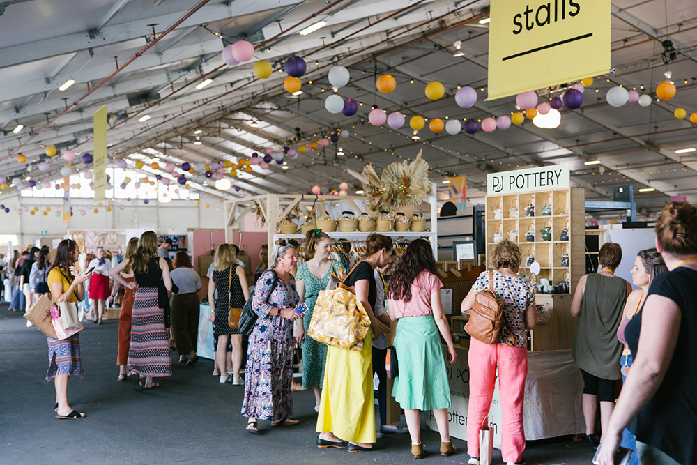 Market goers look at stalls inside the Brisbane Showgrounds marque