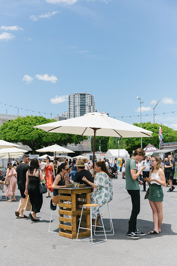 Market goers hang out in the Brisbane sunshine