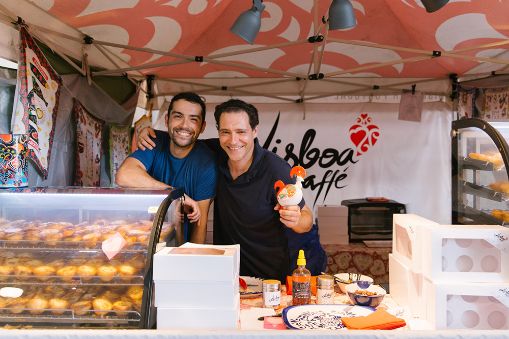 Smiling stallholders selling famous Portuguese tarts