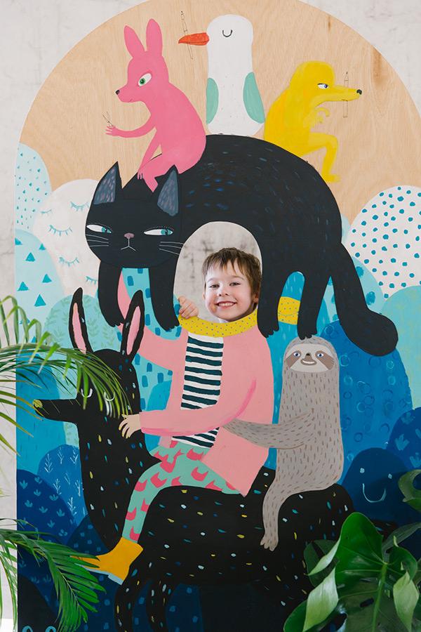 Young boy pokes his head through an artist installation