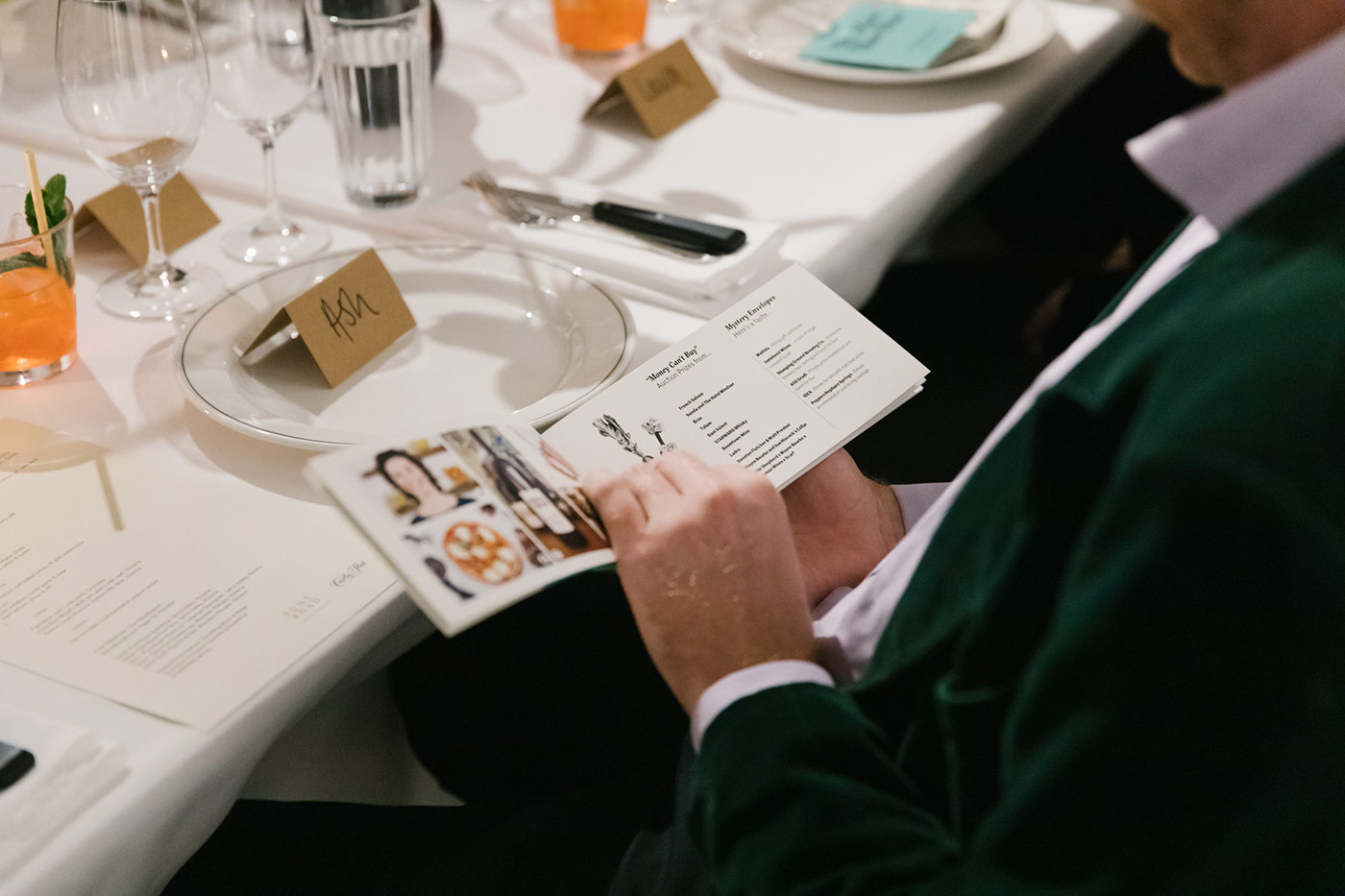 Diners look through the printed catalogue for auction prizes