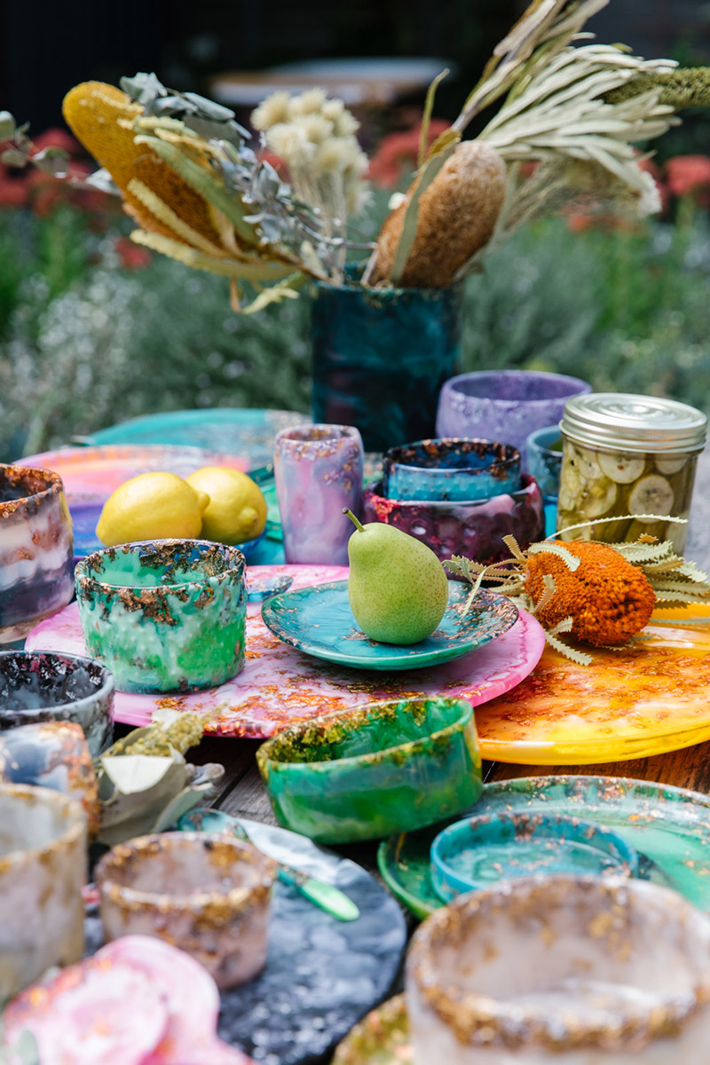 Outdoor wooden table full of colourful resin homewares