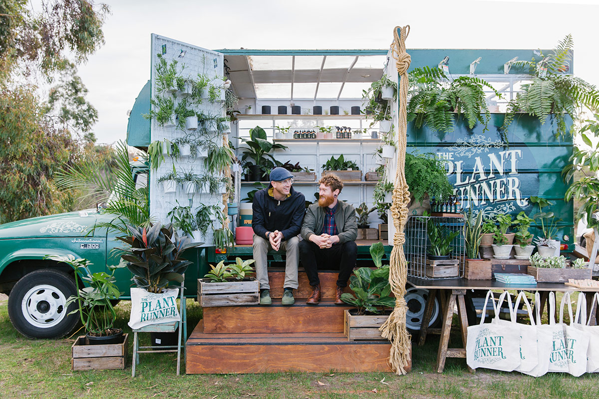 The owners of The Plant Runner mobile pop up shop sit on the steps surrounded by indoor plants and products