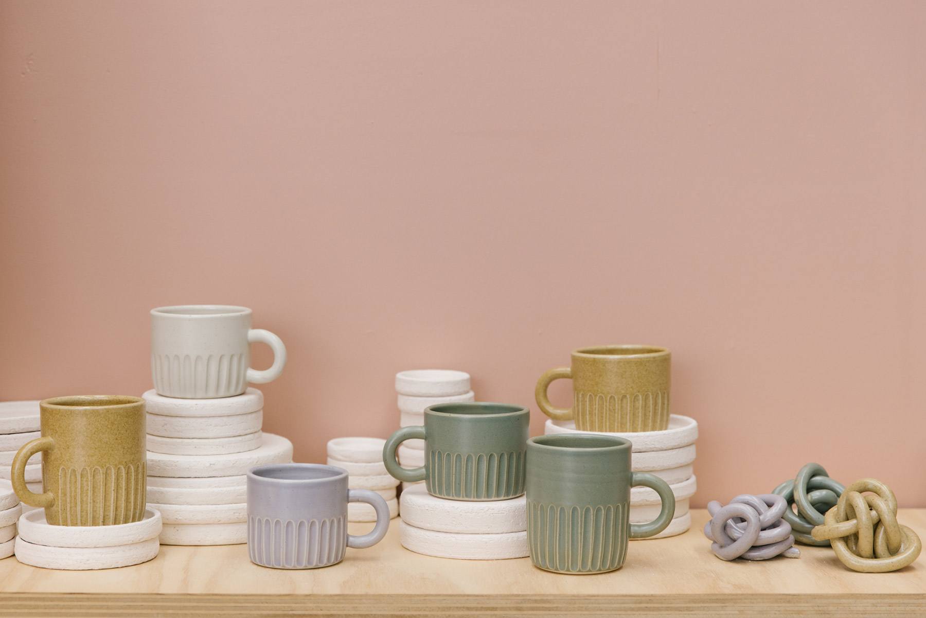 Handmade ceramic mugs by Melbourne ceramicist Arcadia Scott in glazed green, lilac, mustard and cream colours, sitting on a ply bench and white cylindrical plinths with a pastel pink backdrop