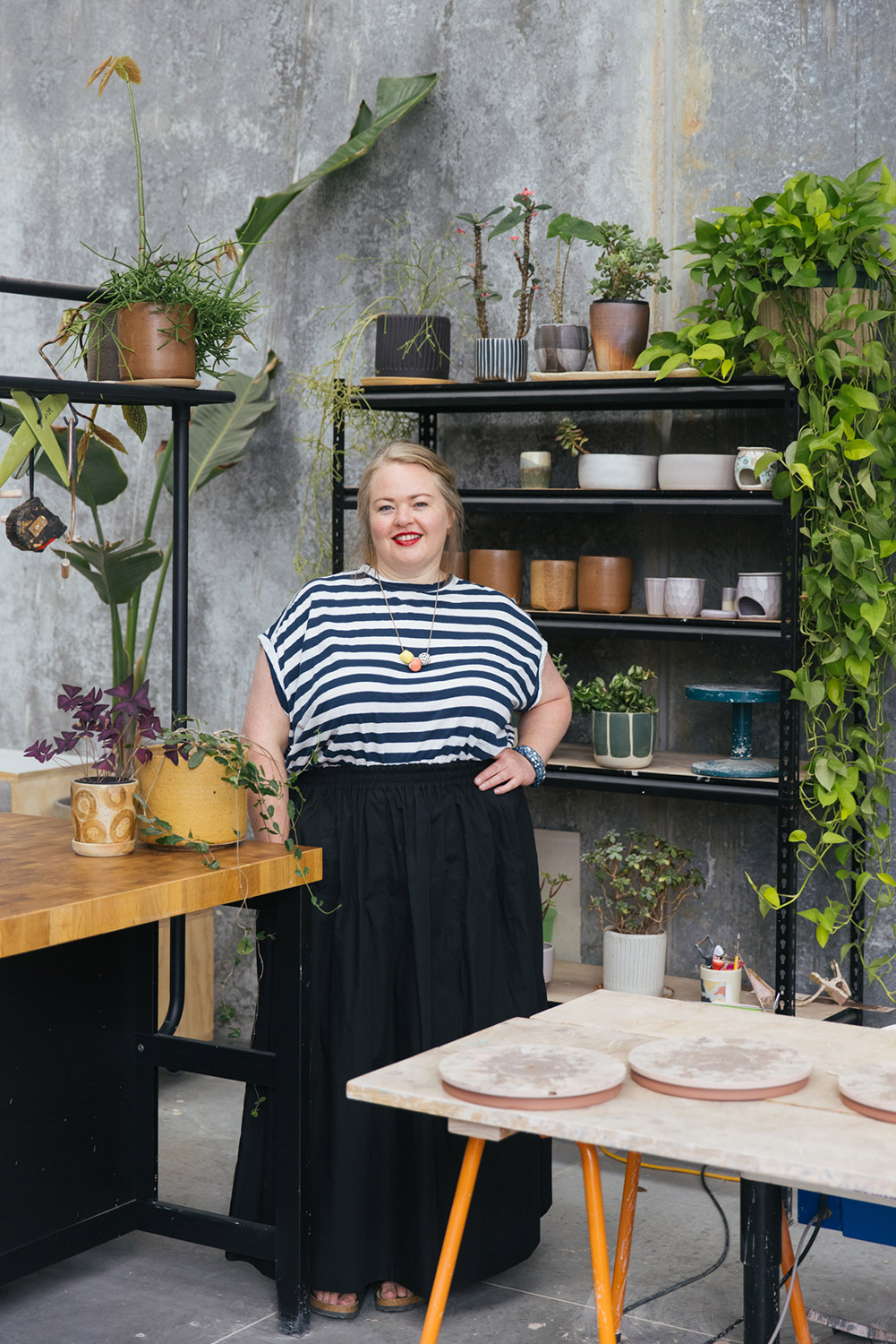 Ceramicist Arcadia Scott stands amongst her studio space, surrounded by shelves of her handmade work and indoor plants