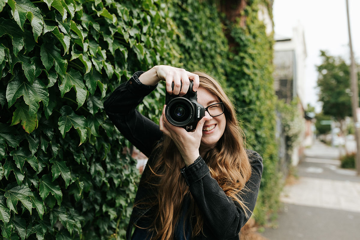 Portrait of Samee Lapham holding her Canon camera to her face to take a photo, smiling. She is standing in front of a green ivy covered wall on the streets of Melbourne, Australia.